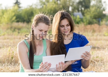 Two teen girls with your Tablet-PC in a nature - stock photo