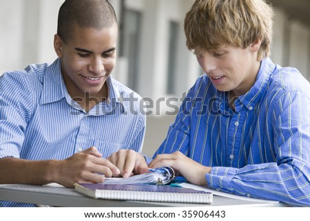 Two teenage boys studying together - stock photo
