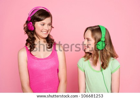 Two teenage friends enjoying music together and looking at the other - stock photo