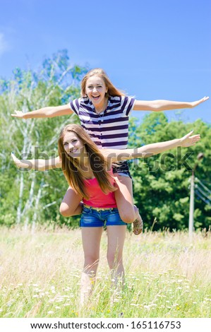 Two teenage girl friends having fun outdoors on summer day happy smiling & looking at camera - stock photo