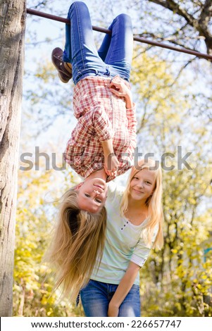 Two teenage girls having fun in park hanging upside down on green countryside rural copy space background - stock photo