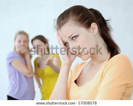 Two teenage girls laugh at their friend. - stock photo