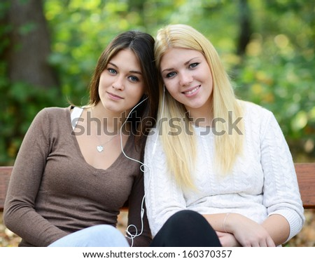 Two teenage girls listening to music outdoors - stock photo