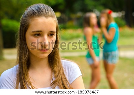 Two teenage girls making fun of the third on beautiful summer day. - stock photo