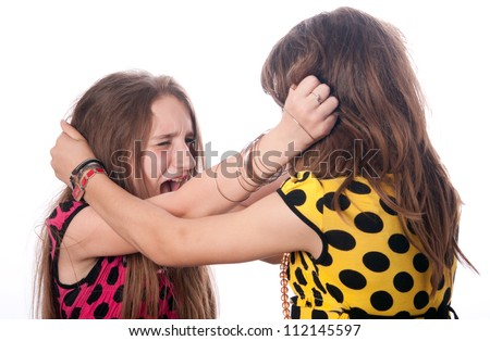 Two teenage girls pulling each others hair out isolated on white. - stock photo