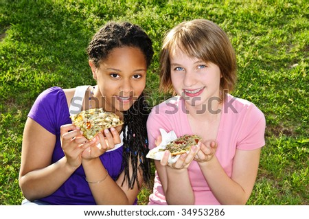 Two teenage girls sitting and eating pizza - stock photo