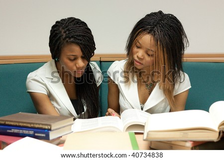 Two teenage girls sitting with books in the library - stock photo