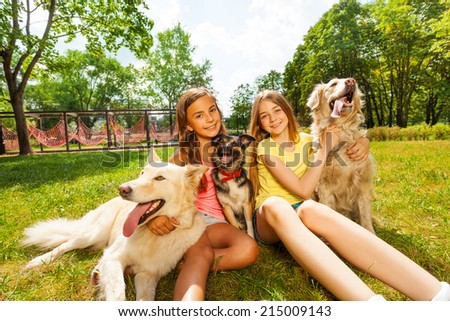 Two teenage girls sitting with three dogs in park - stock photo