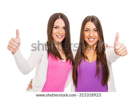 Two teenage girls smiling hugging and gesturing thumbs up. Two brunette young women friends in pink and purple with positive attitude. Isolated on white background. - stock photo
