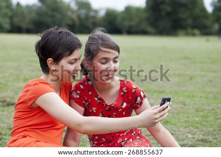 Two teenage girls taking a photo of themselves with a phone - stock photo