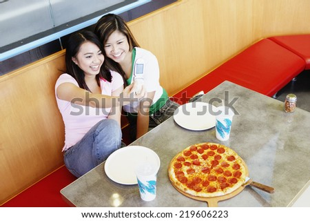 Two teenage girls taking picture with cell phone at pizza restaurant - stock photo