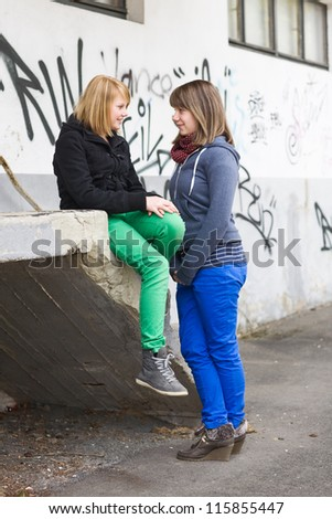 Two teenage girls talking outdoors - stock photo