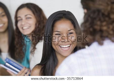 Two teenage girls talking to each other with two others in background. - stock photo