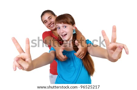 two teenage girls together in studio against white background - stock photo