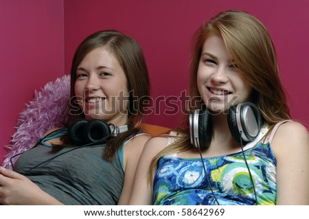 Two teenage girls use cellphone, laptop and a headset in their room. - stock photo