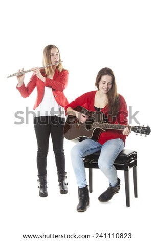 two teenage sisters play flute and guitar in studio with white background - stock photo
