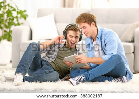 Two teenager boys listening to music with laptop and headphones in living room - stock photo