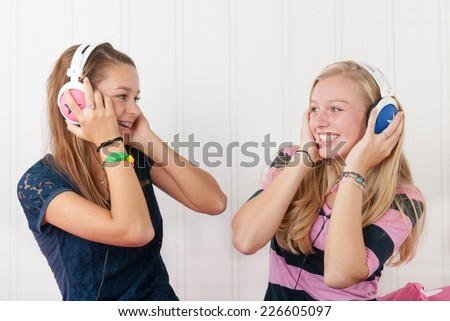 Two teenager girls listening to music with headphones - stock photo