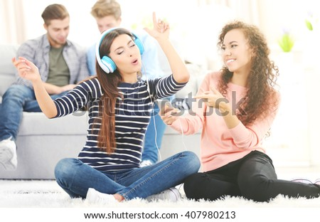 Two teenager girls listening to music with headphones in living room - stock photo