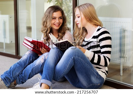 Two teenager girls with books - stock photo