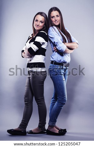 two teenager standing back to back on gray background - stock photo