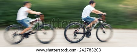 Two teenagers cyclists in traffic on the city roadway. Intentional motion blur - stock photo