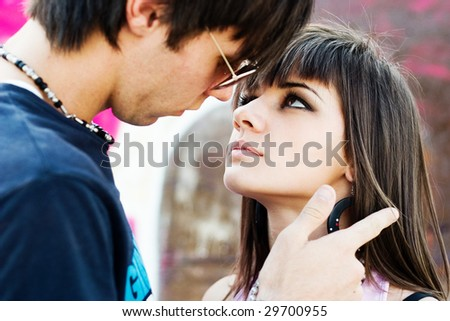 Two teenagers having an intimate moment, with a graffiti background - stock photo