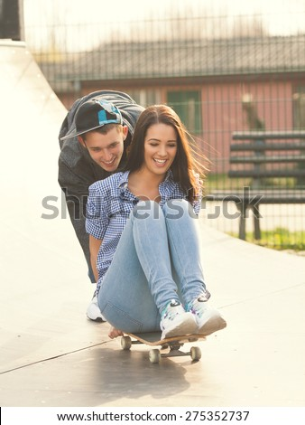 Two teenagers having fun with skateboard in the skate park - stock photo