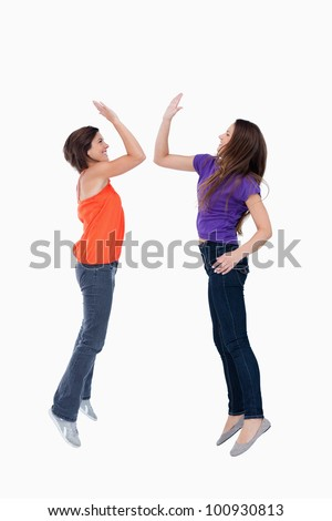 Two teenagers leaping while giving a high-five in the air - stock photo