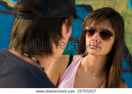 Two teenagers looking at eachother, with a graffiti background - stock photo