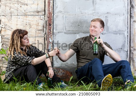 Two teenagers sharing joint and drinking alcohol - stock photo