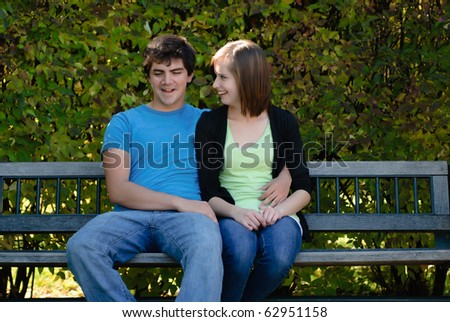 Two teenagers snuggling and sitting on a park bench with leaves in the background. - stock photo