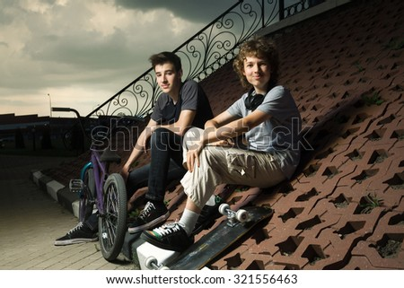 two teenagers talking in the park about extreme sports - stock photo