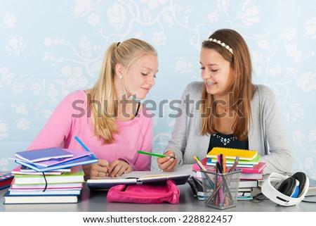 two teengirls sitting at desk making homework together - stock photo