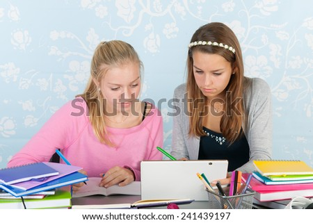 two teengirls sitting at desk making homework together using a digital tablet - stock photo