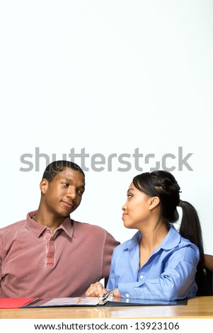 Two Teens are are seated at a desk looking at each other. There are  folders and paper on the desk. Horizontally framed photograph - stock photo