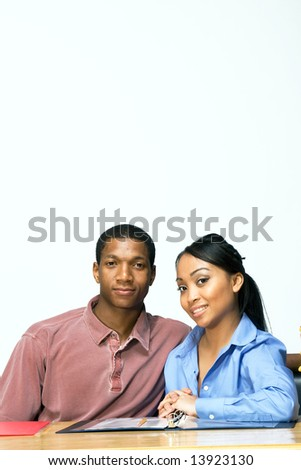 Two Teens are are seated at a desk. The boy is serious and the girl is smiling. There are  folders, and paper on the desk. Vertically framed photograph - stock photo
