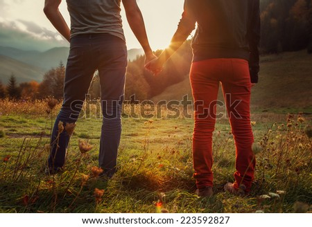 Two teens hand in hand romantic walk by the autumnal mountains - stock photo