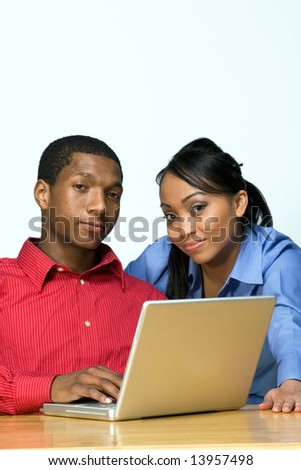 Two Teens Looking serious as they stare ahead and he holds a Laptop Computer. Horizontally framed photograph - stock photo