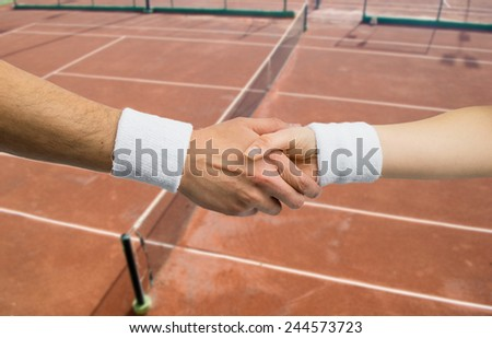 two tennis player take a handshake with a  court tennis in background  - stock photo
