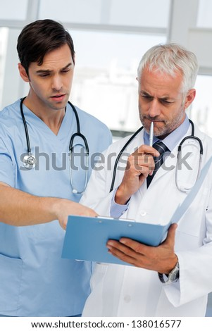 Two thoughtful doctors looking at a file - stock photo