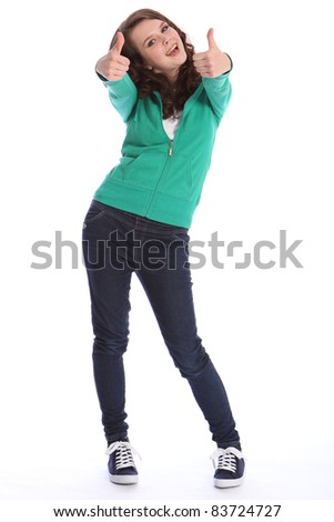 Two thumbs up for big success by happy pretty teenager school girl with long brown hair. She is wearing dark blue jeans and a green sweater. - stock photo