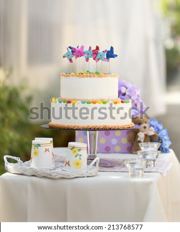 Two tiers birthday cakes on table. Outdoor garden party. - stock photo