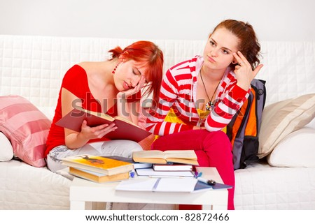 Two tired girlfriends bored to study at living room - stock photo