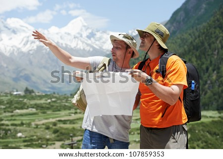 two tjourist trvellers discussing route with map in Himalayas mountains - stock photo