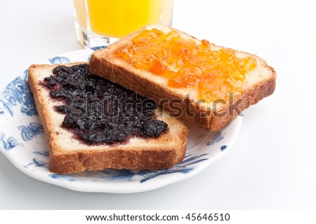 two toasts with jam and a glass of orange juice - stock photo