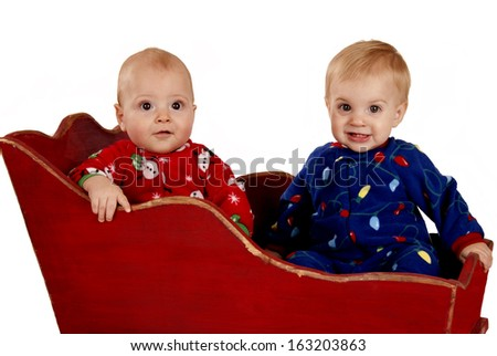 two toddler boys in Christmas pajamas happy - stock photo