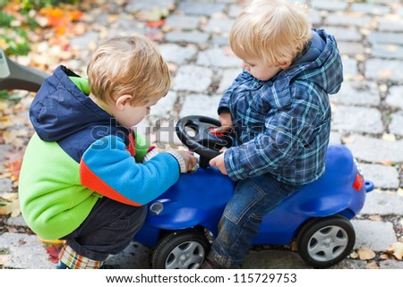 Two toddler boys playing with car in autumn park - stock photo