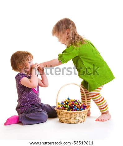 Two toddlers eating sweets from the wicker basket beside - stock photo