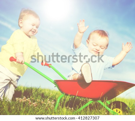 Two toddlers playing together outdoors. - stock photo